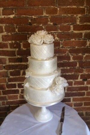 White roses and delicate butterflies on pearlised four tier cakee