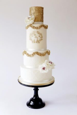 Gold swag cake with gold stencilled monogram, sequins & blush sugar roses. www.gillflettlifestyle.com